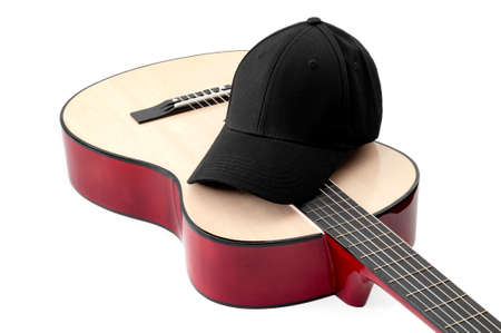 American culture, folk song and country music concept theme with a black baseball cap and an acoustic guitar isolated on white background