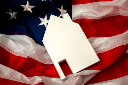 Independence day, land of the free and home of the brave or 4th of July concept theme with a blank slate in the shape of a house and the USA flag with copy space