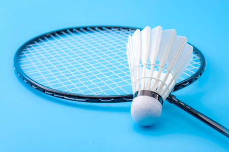 Competitive sports and high performance in tournament match conceptual idea with badminton rackets and shuttlecock (birdie) isolated on blue court background