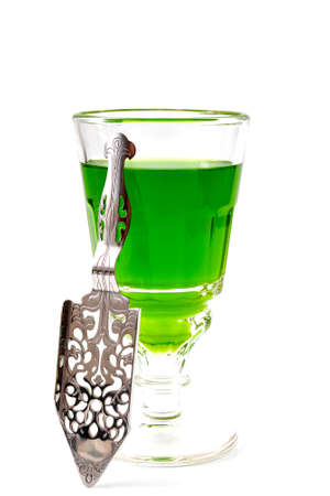 Alcoholic drink, creative stimulant and bohemian lifestyle concept theme with glass of green absinthe and stainless steel spoon isolated on white background