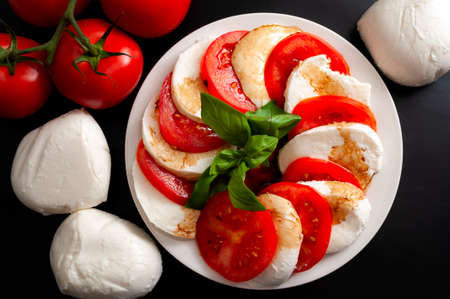 Mediterranean cuisine, fresh vegetarian food and italian culinary art concept with Caprese salad made of mozzarella cheese, rraw tomatoes and basil leafs isolated on black background Stockfoto