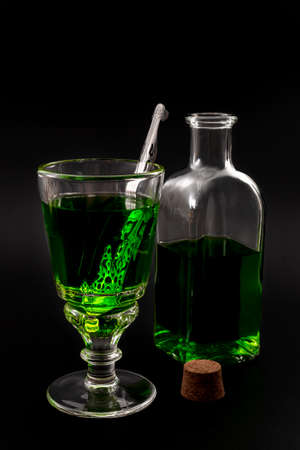 Alcoholic drink, creative stimulant and bohemian lifestyle concept theme with glass of green absinthe and stainless steel spoon next to a vintage bottle and a corck isolated on black background