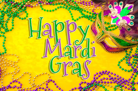 Happy Mardi Gras and Fat Tuesday carnival concept theme with close up on a face mask full of color, feathers and texture and golden, green and purple beads isolated on yellow background with text Stockfoto