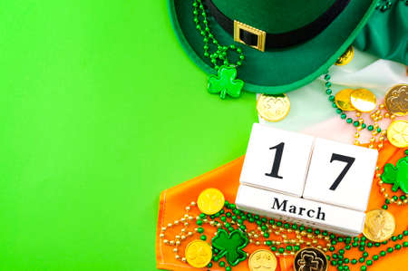 The luck of the Irish meme and Happy St Patricks day concept theme with a calendar, leprechaun hat, beads necklace and gold coins on the Ireland flag isolated on green background with copy space