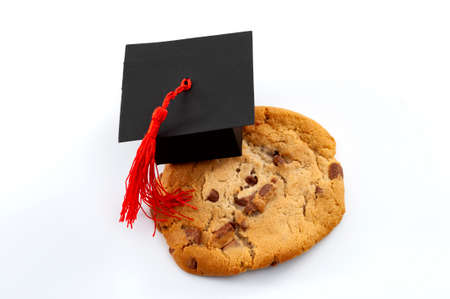 One smart cookie Idiom and a symbol for intelligent concept with close up on a cookie wearing a graduation cap isolated on white background Stockfoto