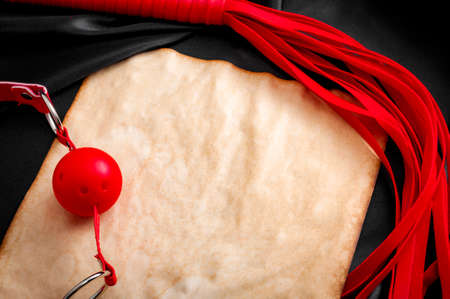 Hedonism, adult games and BDSM lifestyle concept with red ball gag and leather flogger creating a border around a piece of  aged paper on shiny silk in shades of black and dark grey with copyspace