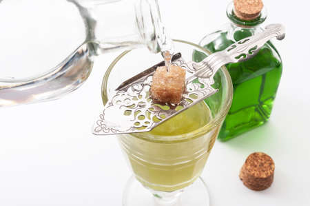 Alcohol, luxurious spirits and dangerous liquor conceptual idea with crystal glass of absinthe, pouring water on stainless steel spoon, sugar cube and green bottle of strong spirit on white background Stockfoto