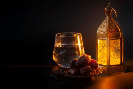 Muslim religious tradition, holy month of Ramadan, Islam and Iftar concept theme with a bowl of dates, prayer beads, glass of water and arabic lantern on black background with copy space Stockfoto