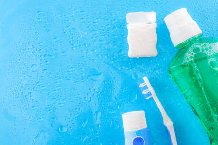 Dental care and oral hygiene concept with a bottle of green mouthwash, toothbrush, dental floss and tube of toothpaste soaked in water droplets, isolated on a blue background with copy space for text