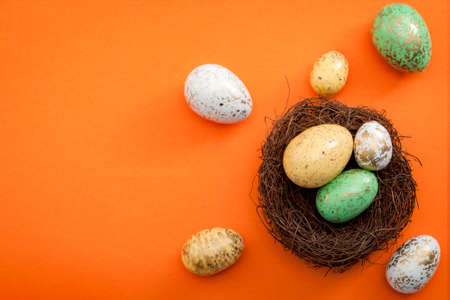 Happy easter and spring meme concept with a colorful image of easter eggs dyed white, green and yellow with gold spots in bird nest against a orange background with copy space