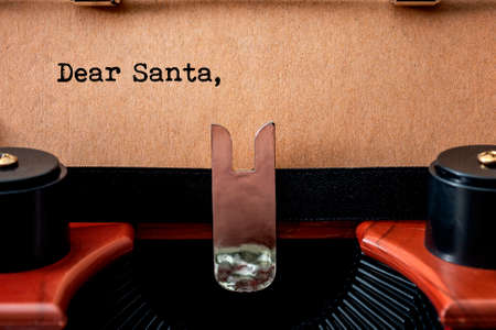 Merry Christmas, old fashioned wish list and Sending a letter to Santa Claus conceptual idea with close up on vintage typewriter and the printed header Dear Santa written on retro brown paper Stockfoto