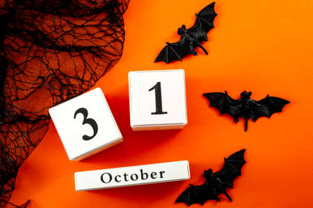 Happy Halloween and fall holiday concept with a calendar showing october 31, bats and black spider web