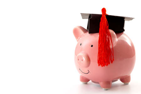 College education costs, tuition financial aid, university graduate economic cost concept theme with close up on piggy bank wearing a graduation cap isolated on white background