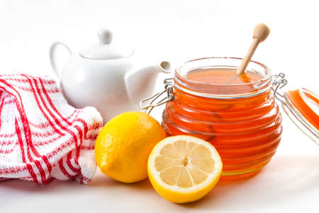Folk natural remedy for flu and cold, strengthen immunity, and alternative medicine concept with close up on a jar of honey with a honey dipper, fresh lemon and a china teapot in the background