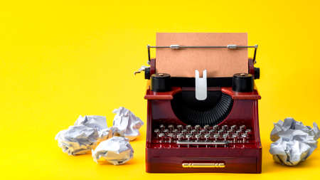 Creative writing, vintage technology and artistic pursuit concept with an retro typewriter surrounded by crumpled paper balls isolated on minimalist bright yellow background with copy space Stockfoto - 152597896