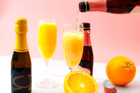 Lush mix drinks, summer alcoholic beverages and refreshing brunch mimosa cocktail concept with orange fruits and champagne pouring from a bottle of bubbly isolated on wooden table and pink background Stockfoto