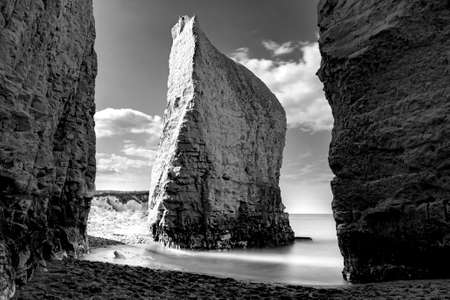 Dreamy tranquility concept with atmospheric monochrome photograph of iconic chalk steep cliff and long exposure of wave flow creating silky fine mist in Botany Bay, Broadstairs, Kent, United Kingdom