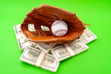 Winning bet on sporting event, money in sport and sports betting conceptual idea with baseball glove holding a ball and wads of money isolated on green background Stockfoto