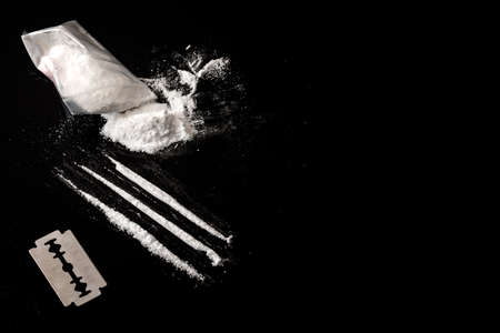 Drug addiction and substance abuse concept theme with lines of cocaine, a small bag with white powder and a blade used to cut each line of narcotics on a dark mirror table with copy space Stockfoto