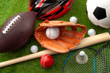 Sports shop, youth athletics and team sport competition conceptual idea with various types balls (soccer, baseball, football, golf ball), wooden bat and bike helmet isolated on green grass background