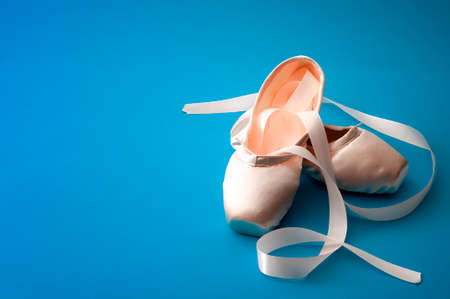 Ballet dancing concept with a pair of silk shoes isolated on minimalist bright blue background Stockfoto