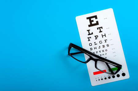 Ophthalmological exam, healthy eyes and ophthalmology concept with a pair of vision glasses and an eye chart isolated on blue background with copy space
