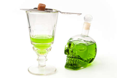 Spirits and alcohol, the green fairy and dangerous liquor conceptual idea with crystal glass of absinthe, silver spoon, sugar cube and skull shaped bottle of strong spirit isolated on white background