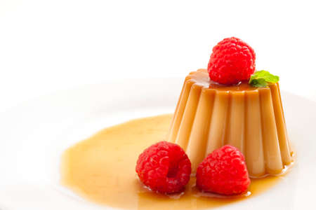 Homemade dessert and smooth custard sweets concept with close up on creme caramel, flan, or caramel pudding covered in sweet syrup and raspberries isolated on white background Stockfoto