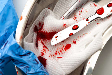 Surgery, OR instruments and dirty operating room concept theme with close up on scalpel, cotton swab, scissors and latex gloves covered in blood in a kidney bowl Stockfoto