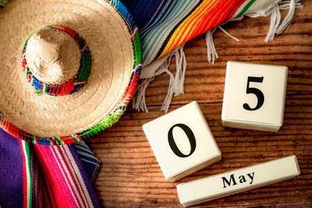 Celebrating Cinco de Mayo and Mexican fiesta conceptual idea with authentic hat (sombrero), traditional colourful rug (serape) and block calendar set to May 5th on wood background Stockfoto