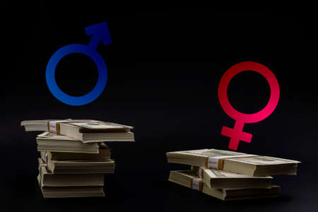 The pay gap and discrimination conceptual idea with the Mars symbol for men and Venus symbol for women on top of unequal stacks of money representing the wage imbalance isolated on black background