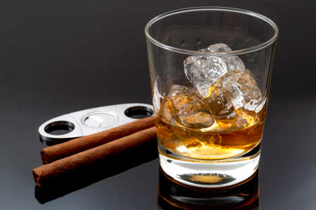 Tobacco smoking and alcohol drinking concept with glass of whiskey on the rocks, cigars, metal cigar cutter and ice on dark background