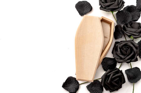 Last goodbye, grief for the deceased and sadness of losing loved ones concept with wood coffin surrounded by black roses isolated on white background with copy space Stockfoto
