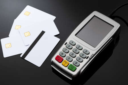 Checkout cashier, financial transaction and electronic payments concept with credit and debit card reader with rubber keyboard next to blank white magnetic cards isolated on shiny black background 版權商用圖片