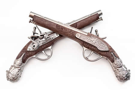 Firearms dating to the american revolution and antique collectables concept with ornate old fashioned dueling flintlock pistols crossed in duel isolated on white background