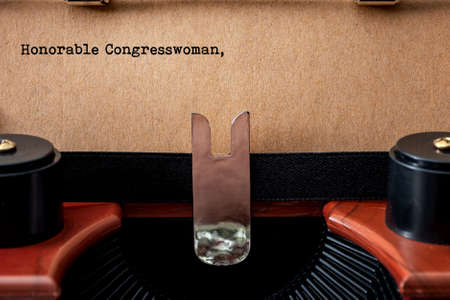 Write to congress, democratic process and voter expressing concerns to elected official conceptual idea with vintage typewriter, old brown paper and the text Honorable Congresswoman