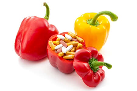 Nourishing diet and replenish vitamins, minerals and supplements through healthy organic food concept with bell peppers full of vitamin and mineral pills isolated on white background