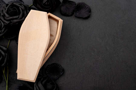Funeral home, death, memento mori (latin - remember that you must die) and grief for the dead conceptual idea with wood coffin surrounded by black roses on dark background with copy space