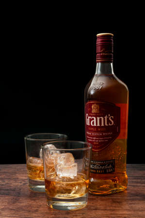 Croydon, UK - January 24, 2020: Illustrative editorial of a bottle of Grant's next to glasses of scotch whiskey on the rocks on wood table and dark black background