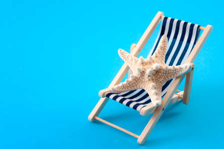 Relaxing on vacation and summer activities concept with a starfish on a lounge chair or lounger isolated on blue minimalist background with copy space