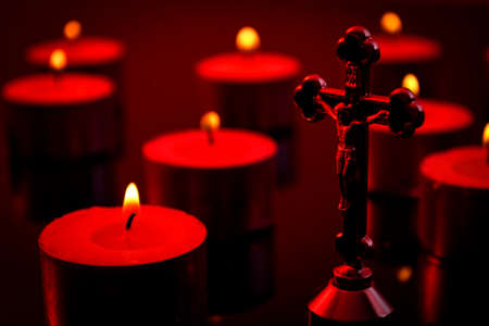 Christianity, faith and religious belief concept with a candlelight scene of a crucifix representing Jesus Christ on the cross and defocused lit candles in the background wit dramatic dark red light Stockfoto