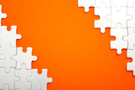 Jigsaw puzzle pieces and business concept with a border made of puzzle pieces on colorful bright orange background with copy space