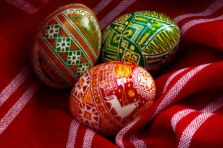 Spring holiday, natural ingredients and happy easter concept with three dyed eggs in a rustic vintage red cloth with each egg having different complex and intricate pattern specific to eastern europe Stockfoto
