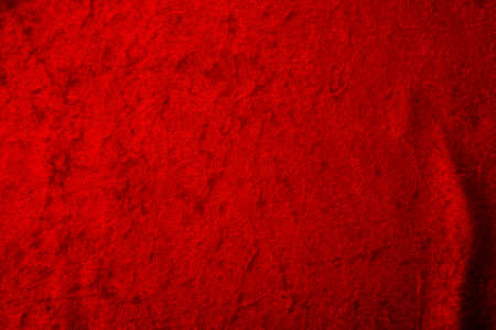 Abstract background and luxury cloth concept with red velvet fabric, mostly stretched but with a couple of  folds or creases with plenty of copy space for text