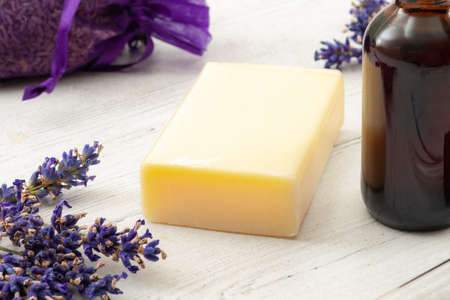 Aromatherapy spa and natural hygiene products concept with homemade soap surrounded by violet pouch of dried lavender, purple flowers and a brown bottle of tincture on a white wooden rustic background Stockfoto