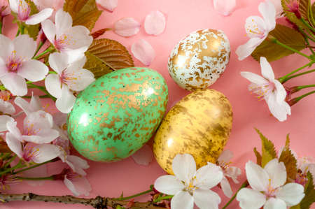 Christianity, spring religious holiday and Christian tradition concept theme with close up on a group of colorful Easter eggs dyed in pastel colors with splotches of gold color and cherry flowers
