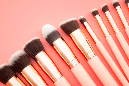 Female fashion and cosmetics, beauty products and makeup school concept theme with a set or kit of make up brushes with each brush a different shape isolated on pink background