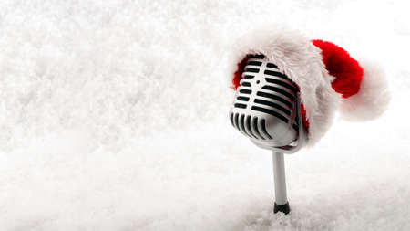 Carols and Christmas music concept with a microphone wearing a santa hat isolated on white snow with copy space Stockfoto