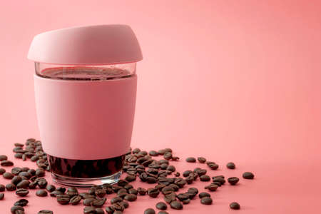Energy drinks, morning routine and stimulant beverages concept glass and rubber cup of java surrounded by roasted coffee beans isolated on pink background with copy space Stockfoto