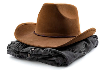American cowboy wear, western design and country fashion conceptual idea with folded pair of black denim jeans and brown cowboy hat isolated on white background Reklamní fotografie